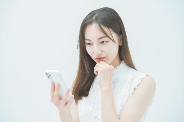 Jonge vrouw die naar een smartphone kijkt met onaangename gevoelens