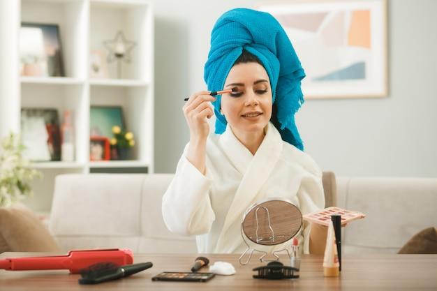 Jonge vrouw die naar een spiegel kijkt die oogschaduw aanbrengt met een make-upborstel die aan tafel zit met make-uphulpmiddelen in de woonkamer