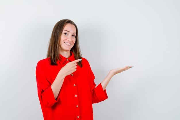 Jonge vrouw die naar haar handpalm wijst in een rode blouse opzij en er vrolijk uitziet, vooraanzicht.