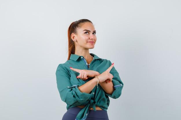 Jonge vrouw die naar links en rechts wijst, omhoog kijkt in een groen shirt en er hoopvol uitziet. vooraanzicht.