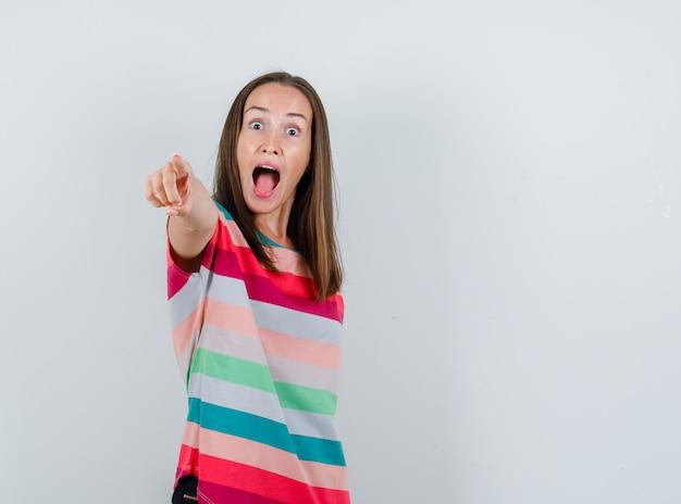 Jonge vrouw die naar voren in t-shirt richt en gek kijkt. vooraanzicht.