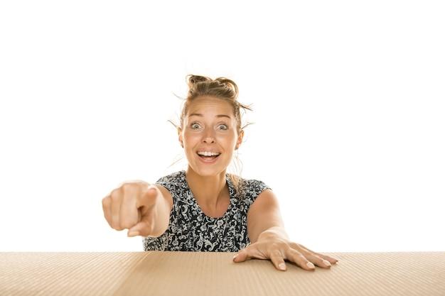 Jonge vrouw die naar voren wijst op een houten tafel