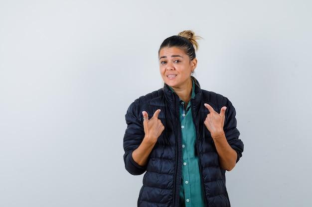 Jonge vrouw die naar zichzelf wijst in hemd, pufferjack en er vrolijk uitziet, vooraanzicht.