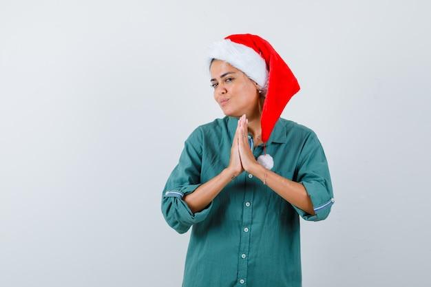 Jonge vrouw die namaste-gebaar in overhemd, kerstmuts toont en er hoopvol uitziet, vooraanzicht.