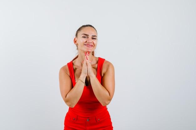 Jonge vrouw die namaste-gebaar in rood mouwloos onderhemd, broek toont en vreedzaam, vooraanzicht kijkt.