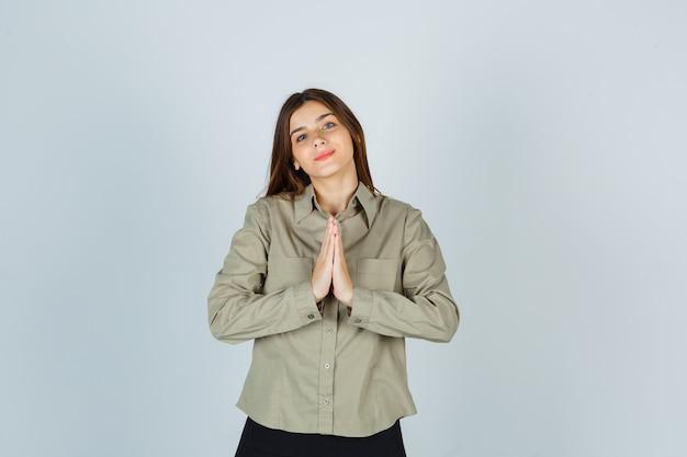 Jonge vrouw die namaste-gebaar in shirt, rok toont en er hoopvol uitziet, vooraanzicht.