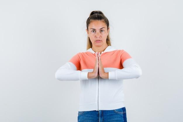 Jonge vrouw die namaste gebaar in zip hoodie, jeans toont en kalm kijkt