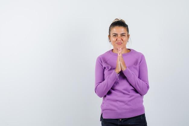 Jonge vrouw die namaste-gebaar toont