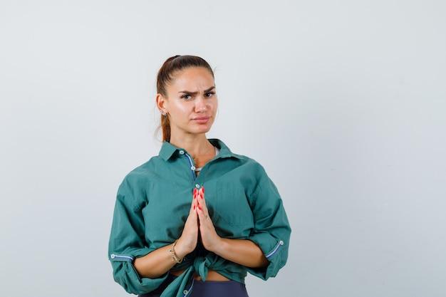 Jonge vrouw die namastegebaar in groen overhemd toont en nadenkend, vooraanzicht kijkt.