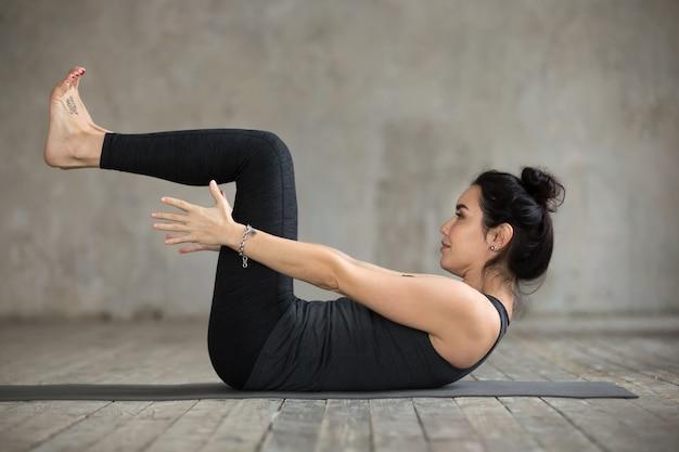 Jonge vrouw die navasana oefening doet