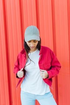 Jonge vrouw die neer terwijl het houden van rood jasje die zich tegen metaalachtergrond bevinden kijkt