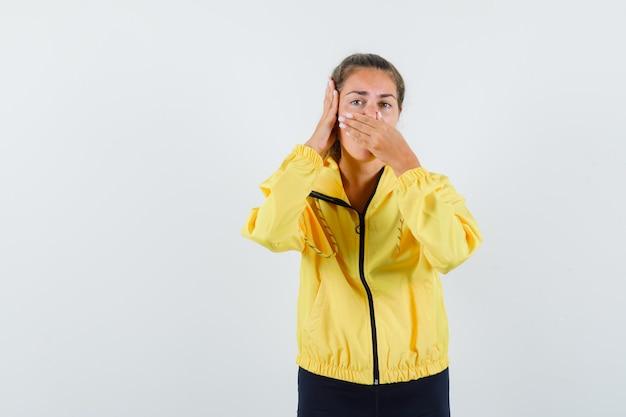 Jonge vrouw die neus knijpt als gevolg van stank en hand op oor in geel bomberjack en zwarte broek drukt en op zoek gekweld