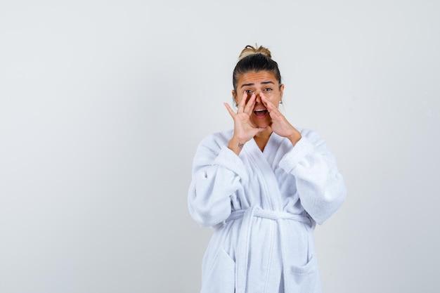 Jonge vrouw die neus met hand in badjas drukt en verrast kijkt