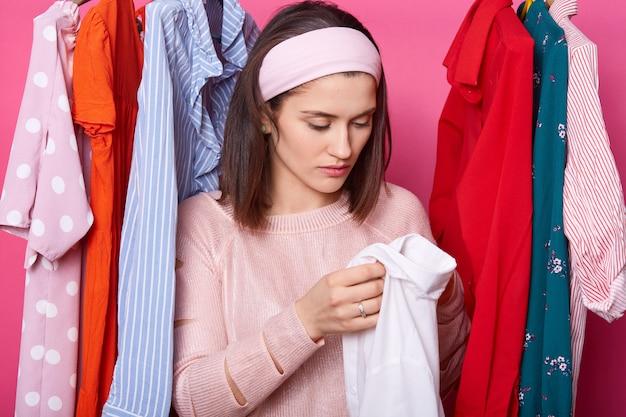 Jonge vrouw die nieuw overhemd houdt, dat kleren kiest van een rek