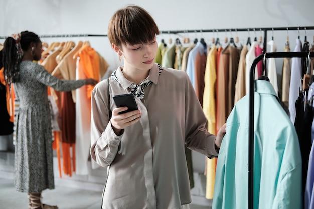 Jonge vrouw die nieuwe overhemden op het rek kiest terwijl ze haar mobiele telefoon in het winkelcentrum gebruikt