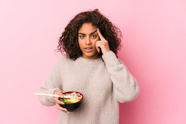 Jonge vrouw die noedels eet die een teleurstellingsgebaar met wijsvinger tonen