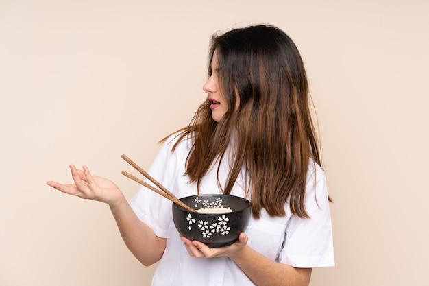 Jonge vrouw die noedels over geïsoleerde achtergrond eet