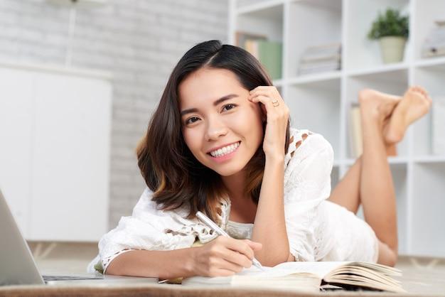 Jonge vrouw die nota's in haar notitieboekje maakt dat camera bekijkt