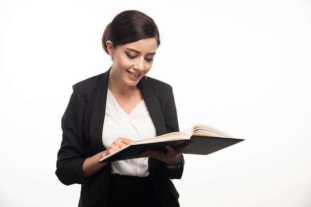 Jonge vrouw die nota's op witte achtergrond controleert. hoge kwaliteit foto