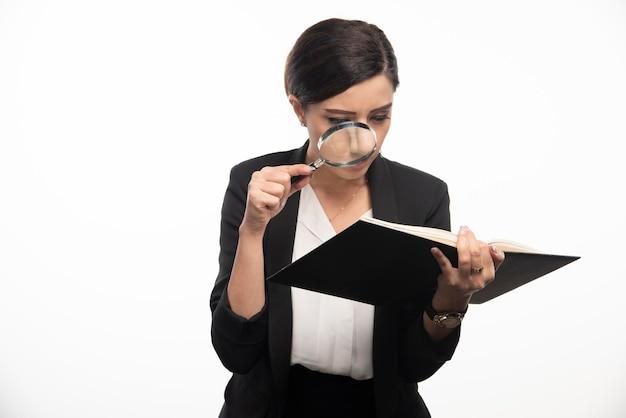 Jonge vrouw die notitieboekje met vergrootglas bekijkt. hoge kwaliteit foto