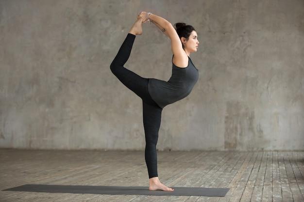 Jonge vrouw die oefening natarajasana doet