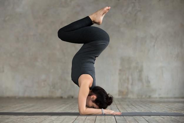 Jonge vrouw die oefening pincha mayurasana doet