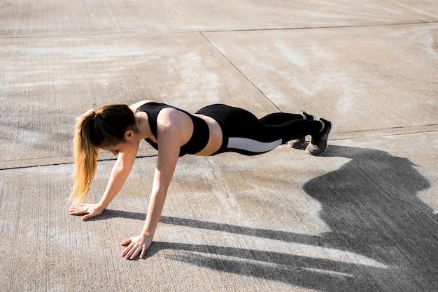 Jonge vrouw die oefeningen doet bij de straat