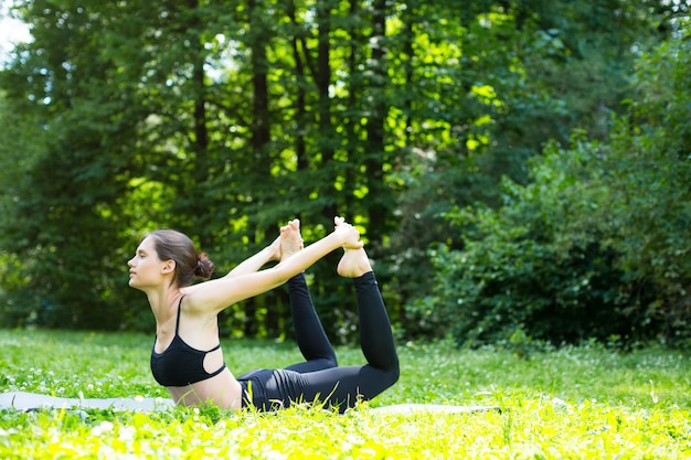 Jonge vrouw die oefeningen in het park doet.