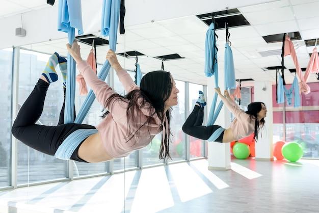 Jonge vrouw die oefeningen maakt van vliegende yoga