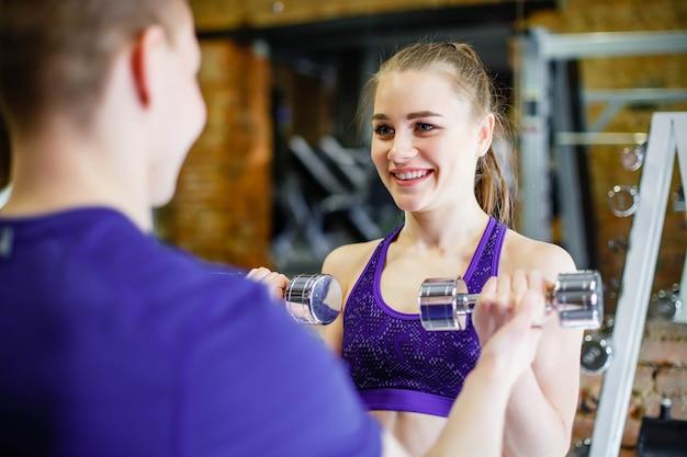 Jonge vrouw die oefeningen met domoren in de gymnastiek met een persoonlijke trainer doet
