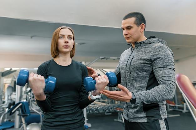 Jonge vrouw die oefeningen met persoonlijke instructeur in gymnastiek doet.