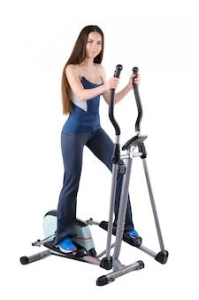 Jonge vrouw die oefeningen op elliptische trainer doet
