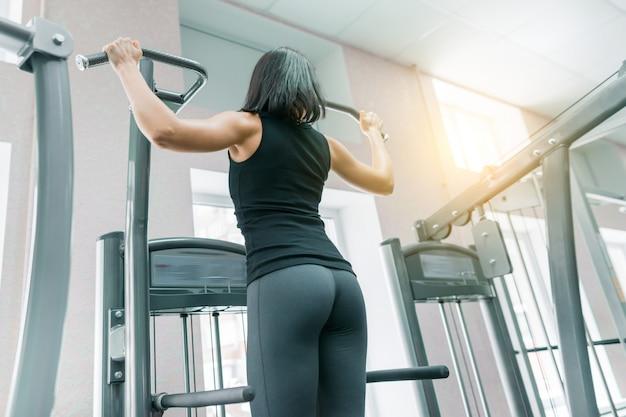 Jonge vrouw die oefeningen voor de rug op geschiktheidsmachine doen in gymnastiek