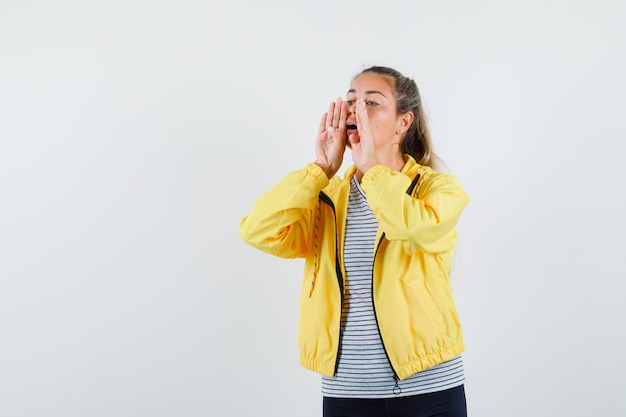 Jonge vrouw die of iets in t-shirt, jasje, vooraanzicht schreeuwt.