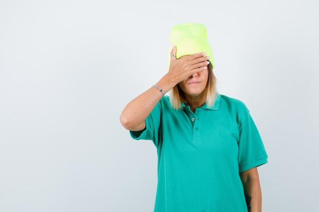Jonge vrouw die ogen bedekt met hand in polo t-shirt, muts en nieuwsgierig kijkt, vooraanzicht.