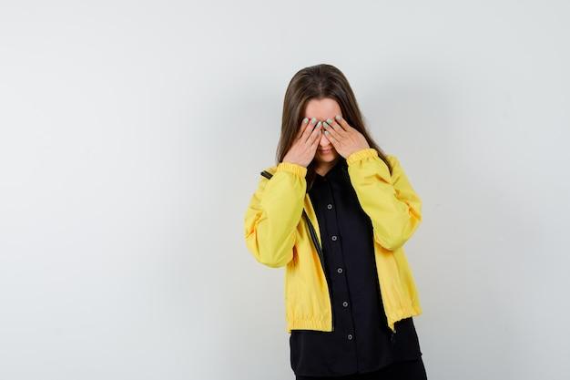 Jonge vrouw die ogen bedekt met handen en zich schaamt?