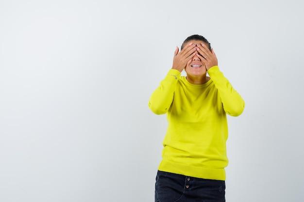 Jonge vrouw die ogen bedekt met handen in gele trui en zwarte broek en er gelukkig uitziet