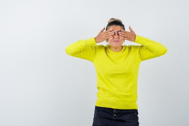 Jonge vrouw die ogen bedekt met handen in gele trui en zwarte broek en er serieus uitziet