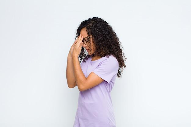 Jonge vrouw die ogen behandelt met handen met een droevige, gefrustreerde blik van wanhoop, huilend, zijaanzicht over witte muur