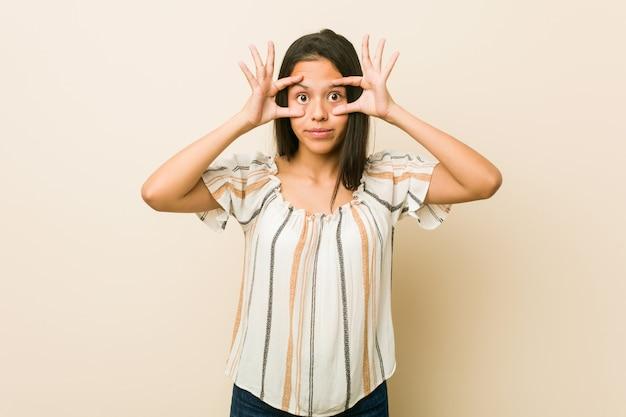 Jonge vrouw die ogen houdt geopend om een succeskans te vinden