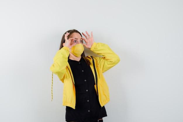 Jonge vrouw die ogen opent met vingers