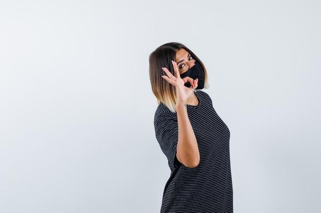 Jonge vrouw die ok teken in zwarte kleding, zwart masker toont en ernstig kijkt. vooraanzicht.