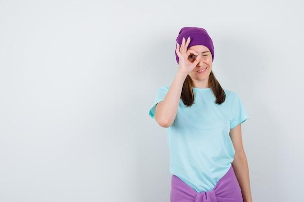 Jonge vrouw die ok teken op oog in t-shirt, beanie toont en nieuwsgierig kijkt. vooraanzicht.