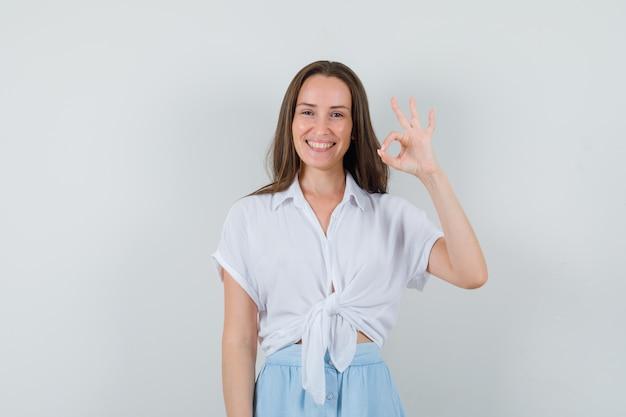Jonge vrouw die ok teken toont en in witte blouse en lichtblauwe rok glimlacht en vrolijk kijkt