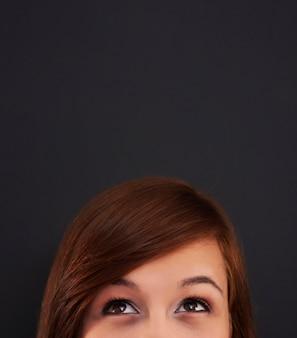 Jonge vrouw die omhoog bord bekijkt