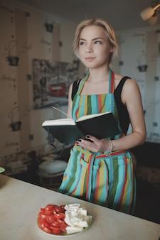Jonge vrouw die omhoog in een receptenboek kijkt
