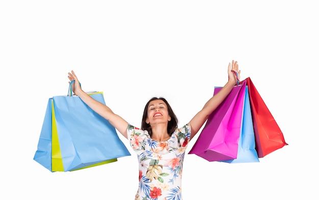 Jonge vrouw die omhoog met het winkelen zakken op witte achtergrond kijkt