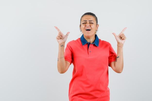 Jonge vrouw die omhoog met wijsvingers in rood t-shirt richt en geamuseerd kijkt. vooraanzicht.