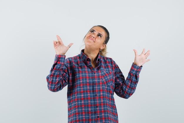 Jonge vrouw die omhoog wijst en hand uitrekt als stopbord in gecontroleerd overhemd toont en er mooi uitziet. vooraanzicht.