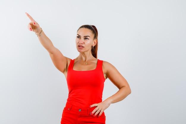 Jonge vrouw die omhoog wijst, hand op taille in rode tanktop, broek houdt en weemoedig, vooraanzicht kijkt.